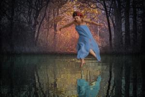 girl levitating water lake reflection